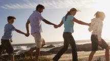 une famille qui se tient la main sur la plage